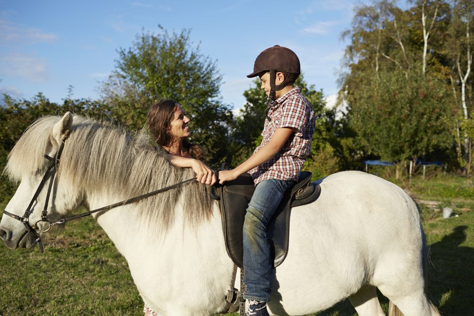 Mother helping son with horse riding