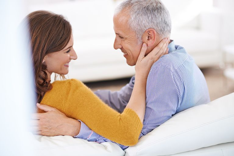 man and woman smiling on couch