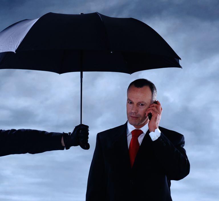 Man holding umbrella over businessman using mobile phone