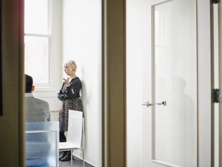 Senior businesswoman leading discussion with coworkers in glass walled conference room
