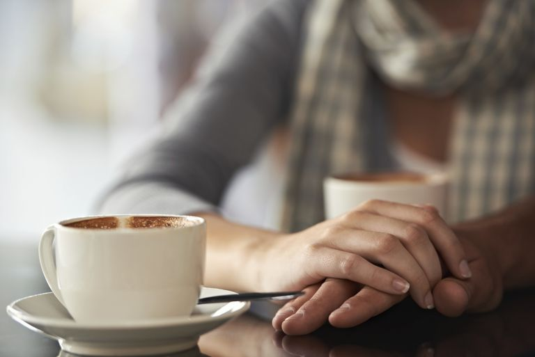 Woman sitting in coffee shop with another woman, carefully sharing her pregnancy news