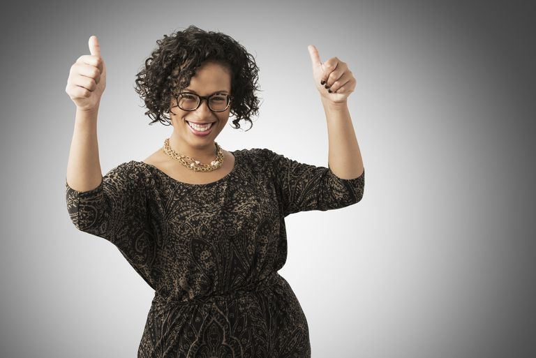 Mixed race woman cheering with thumbs up