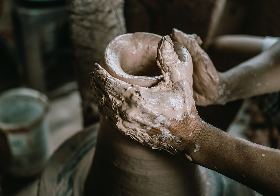 Hands of potter to fashion a piece of pottery from raw clay.