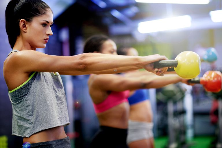 a group of women working out with kettle bells at the gym