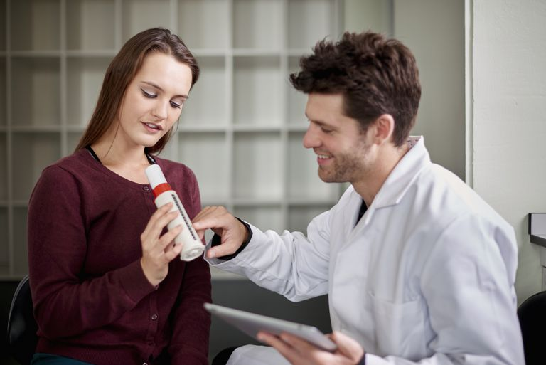 Young woman using peak flow meter, young man assessing results