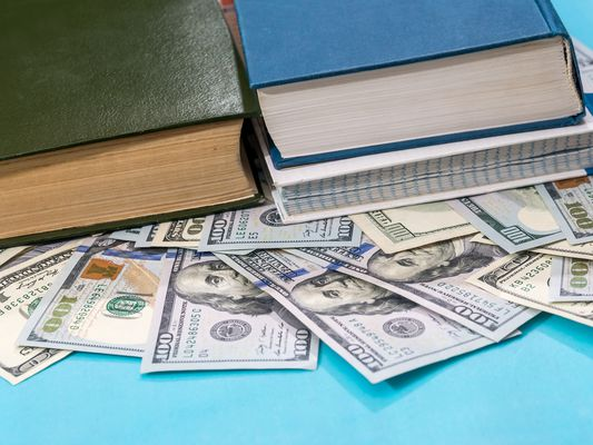 dollar and book on blue background