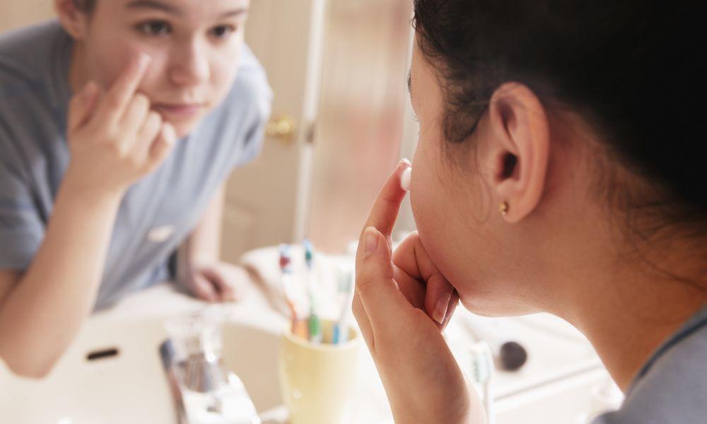 Teen girl applying acne cream in mirror