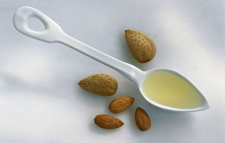 Almonds and spoonful of almond oil, close up