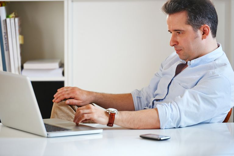 frustrated man at desk with laptop