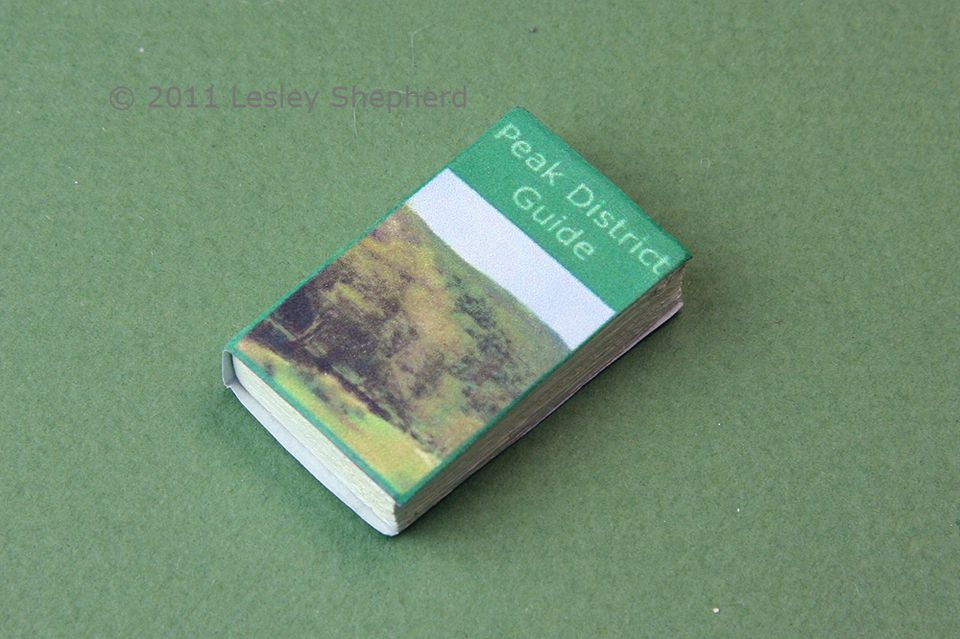 A simple dolls house book made from a paper cover and textured painted wood.