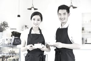 a male and female couple working together in a coffee shop