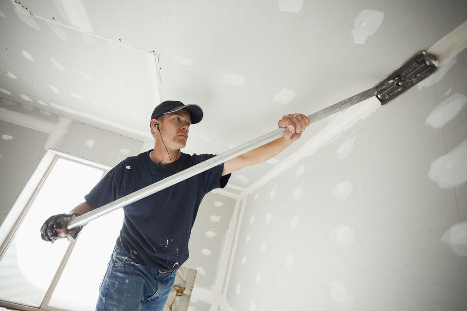 USA, Utah, Lehi, Drywall worker applying tape to corner between wall and ceiling