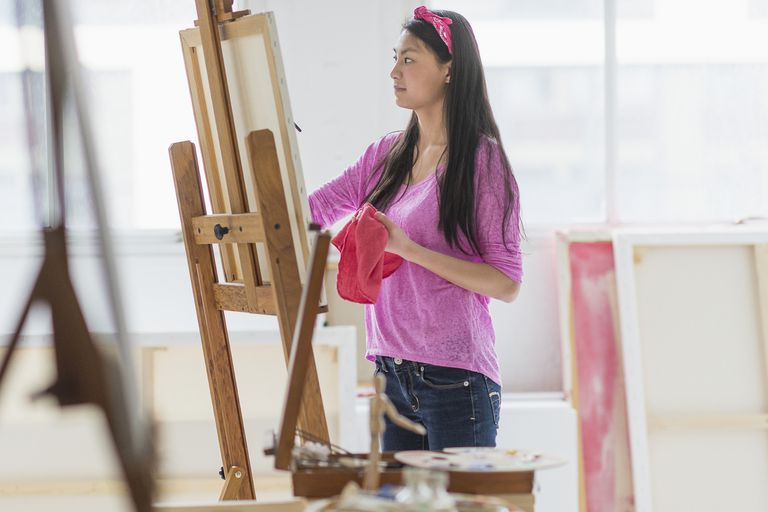 A teenage girl paints in a studio.