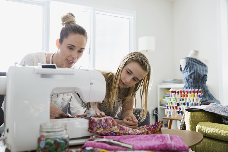 Mother and daughter sewing together