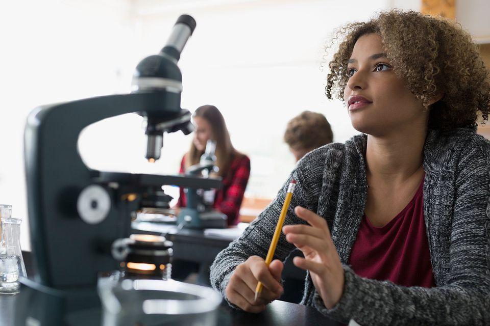 Focused high school student microscope listening science classroom.