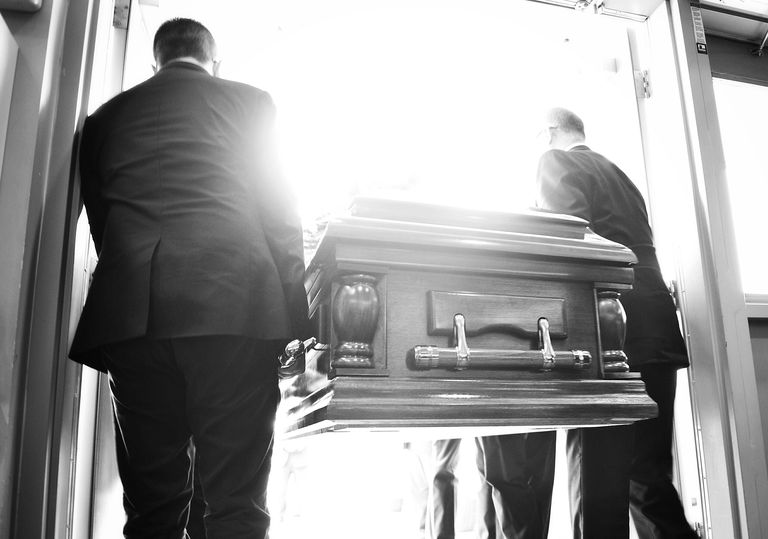 Two men carry a casket from a church. Rates of mortality among middle aged white Americans have spiked in recent years.