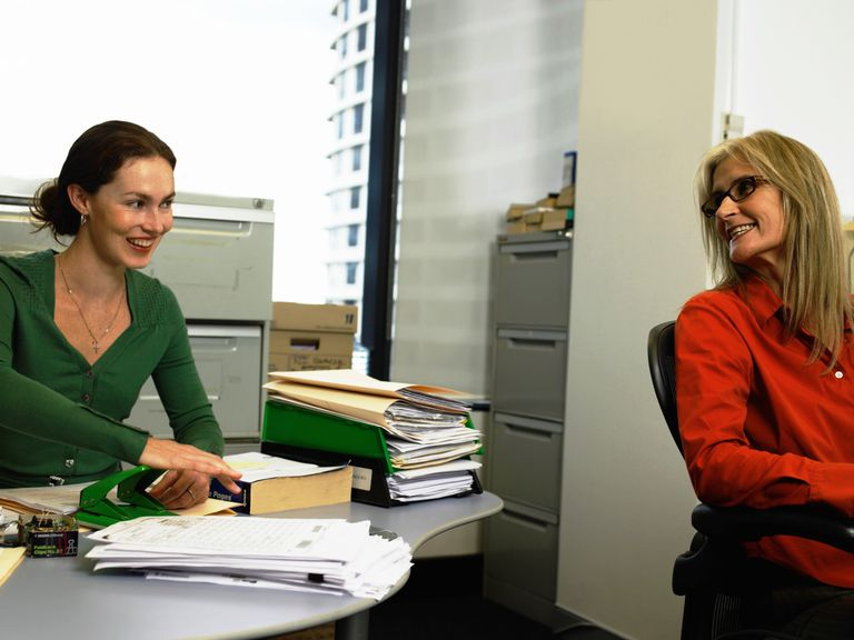 Young woman at desk, looking at mature woman in office, smiling