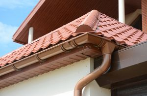 Close up on roof gutter holder and guttering downspout pipe