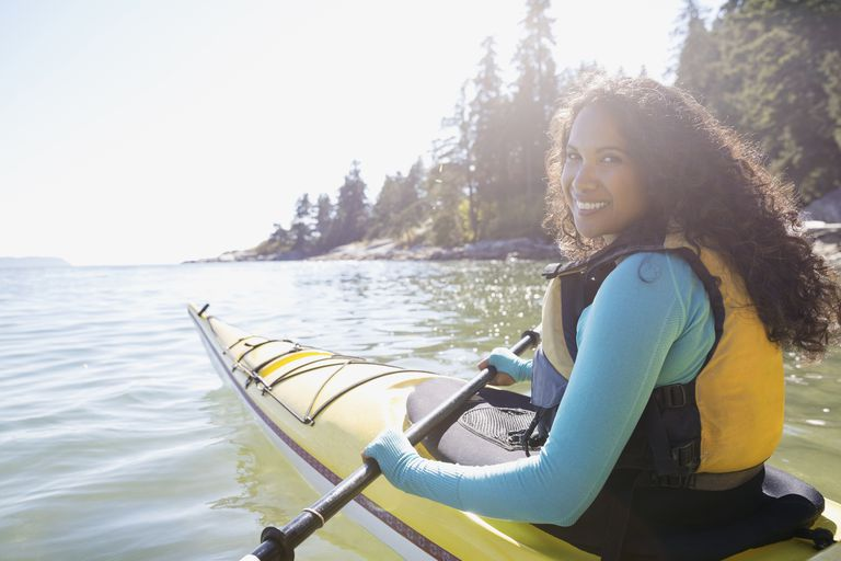 Portrait of smiling woman kayaking in ocean