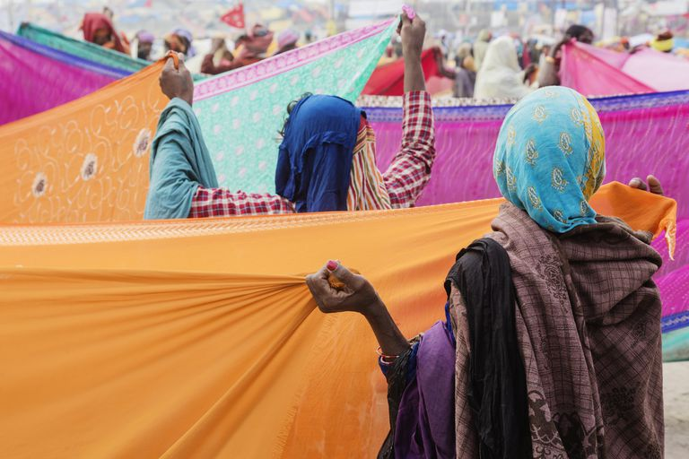 Women holding colorful fabric at festival, Allahabad, Uttar Pradesh, India