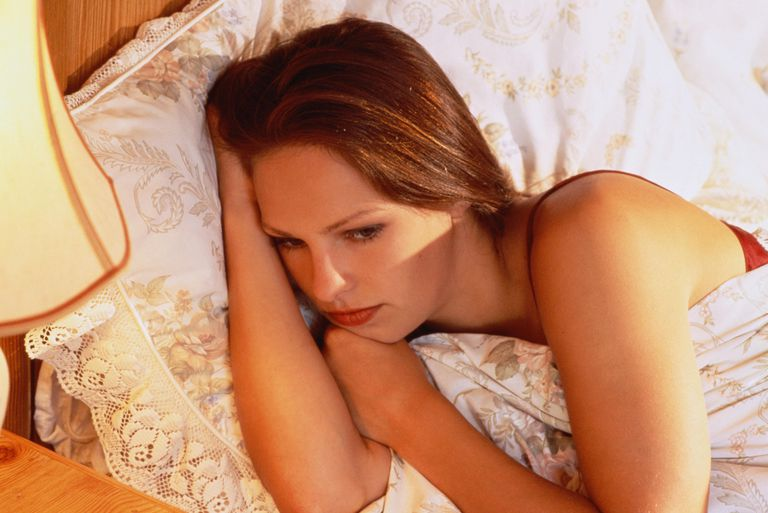 YOUNG WOMAN LYING IN BED AWAKE