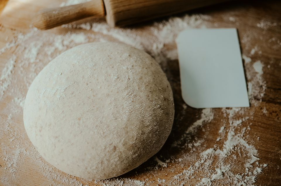 Whole wheat pizza dough shaped into ball on floured wooden background