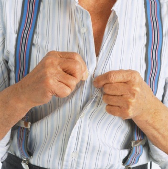 elderly man trying to button his shirt