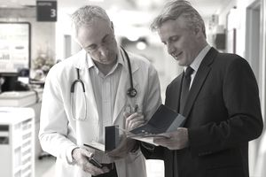 Doctor and businessman talking in hospital