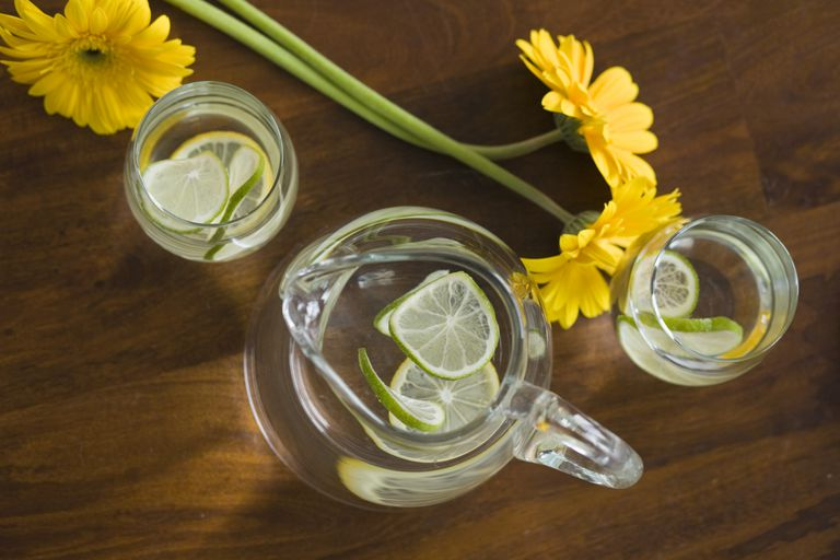 pitcher of water with slices of lemon and lime