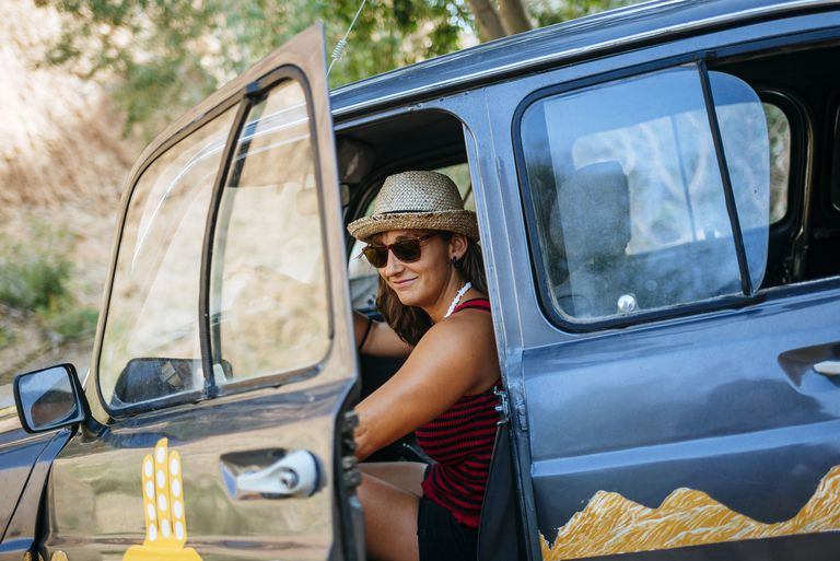 Morocco, Ouarzazate, portrait of smiling woman getting on her car