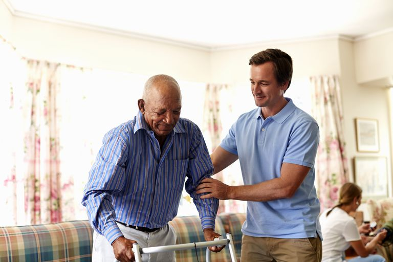 Man helping an older person rise from a couch.