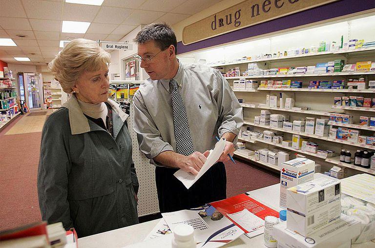 Pharmacist, William Hewitt, (R) speaks with Aase Kjos-Hansen about her options under the new Medicare prescription drug benefit program