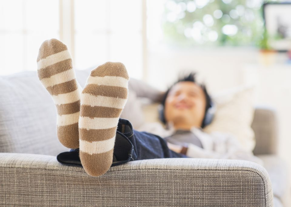 Teenage boy (16-17) lying on sofa and listening to music