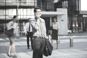 Smiling businessman talking on cell phone outside urban building