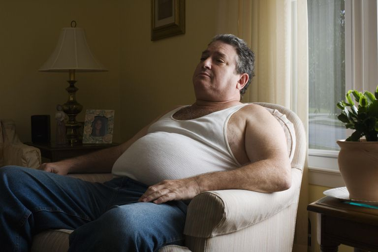 Mature overweight man sitting in armchair