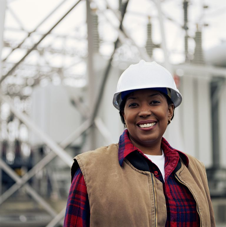 Woman wearing hard hat in front of power station, portrait