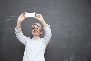 Older woman taking a selfie with her mobile phone.