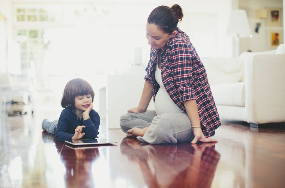 mother and son using ipad sitting on floor