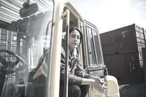 Female forklift driver in sunny industrial container yard