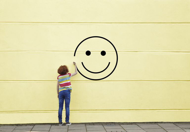 Woman drawing a smiley face on a yellow wall