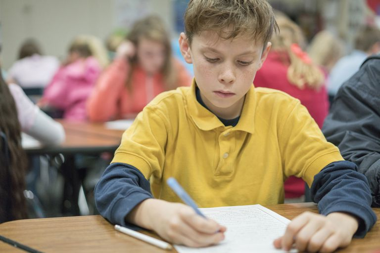 Caucasian student writing at desk in classroom