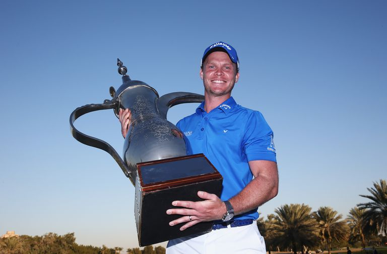 Danny Willett of England poses with the trophy after his victory in the 2016 Omega Dubai Desert Classic