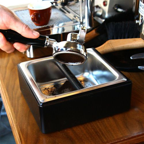 An image of a barista knocking the puck from the portafilter into the knock box.