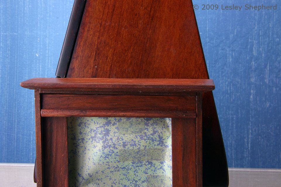 Faux mahogany finish on a dolls house fireplace compared to a piece of finished fine mahogany
