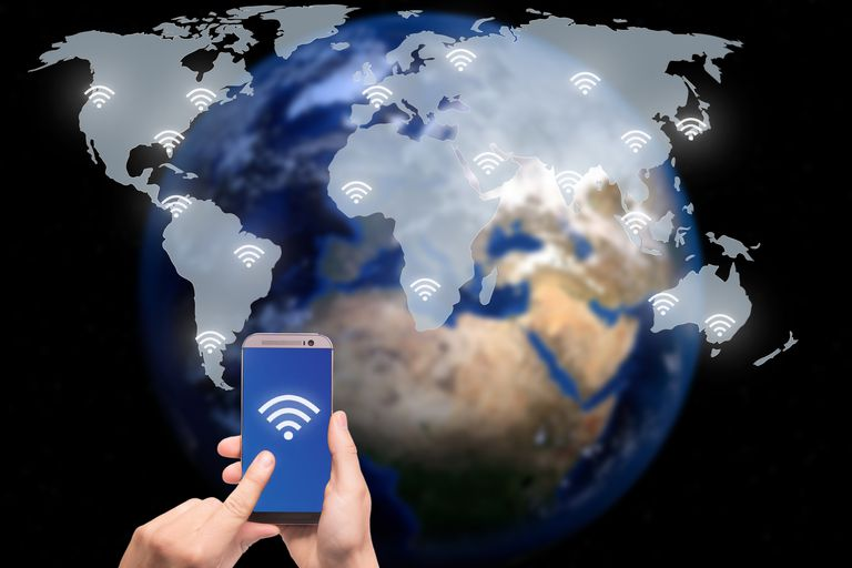 Hand holding smart phone on world map network and wireless communication network, abstract image visual, internet of things.Elements of this image furnished by NASA