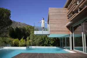 Woman standing on balcony over swimming pool