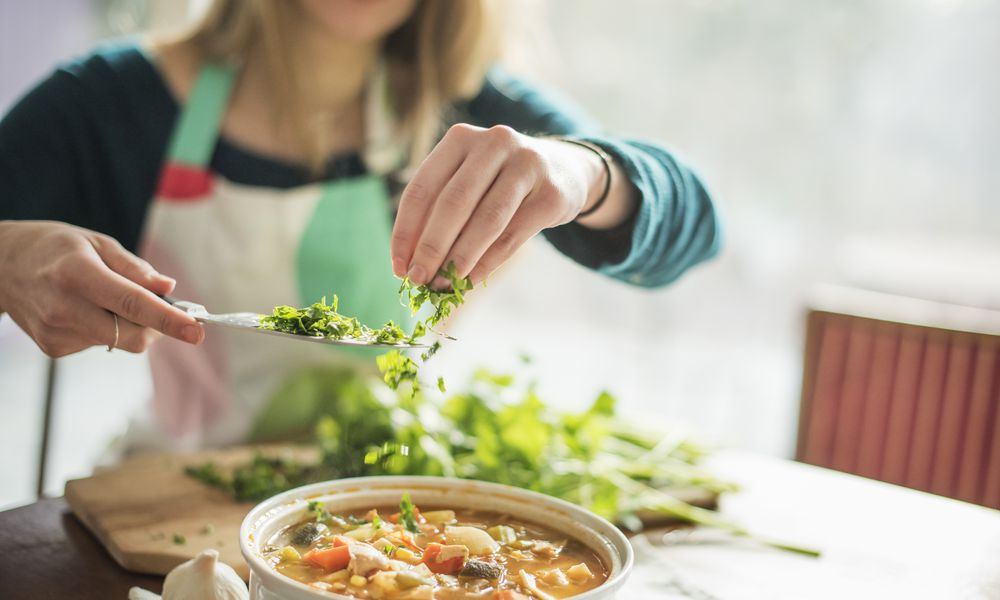 A woman wearing an apron, sitting at a table, sprinkling herbs into a bowl of vegetable stew.