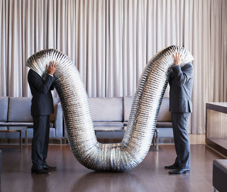 Businessmen with their heads inside metal tubing.