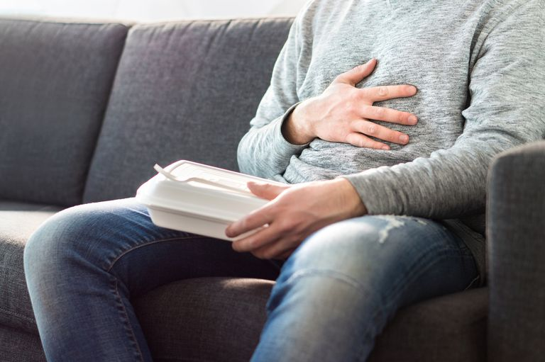 Man holding stomach with heartburn after eating