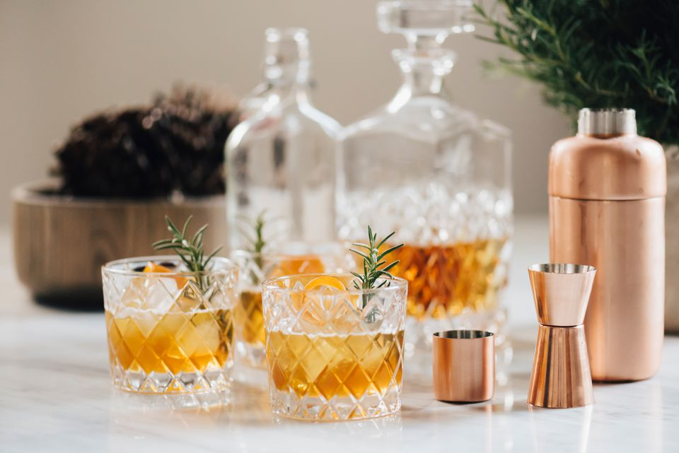 Bourbon cocktails on marble countertop with crystal decanters and rose gold bar tools